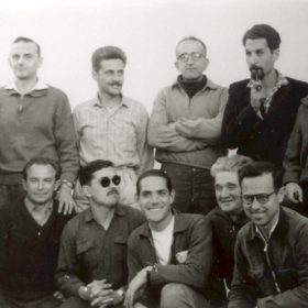 Camp d'internement de Lodi, 1957. Une partie de l'équipe d'Alger Républicain. Debout, de gauche à droite: X, Paul Amar, X, René Azoulay, Jean-Pierre Saïd, Alexandre Valero. Accroupis: René Duvalet, Vincent Ivorra, Henri Zannettacci, Raymond Neveu, X.