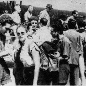 Alger, été 1953. Accueil des délégués algériens de retour du festival mondial de la jeunesse de Bucarest. À gauche, Jean-Pierre Saïd, un carnet et un crayon à la main, s'entretient avec une déléguée pour Alger Républicain. À droite, Sadek Hadjerès