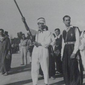 Varsovie, juillet 1955. La délégation algérienne lors du défilé d'ouverture du festival mondial de la jeunesse, avec des vêtements d'apparat algériens. Au second plan à droite, tête nue, Jacqueline Schecroun. Devant elle, Mireille Saïd est vêtue d'un haïk. Le metteur en scène Mustapha Kateb est au second plan, au centre, derrière le porteur de drapeau.